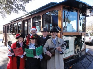The Austin Carolers serenade with an old Armadillo Trolley